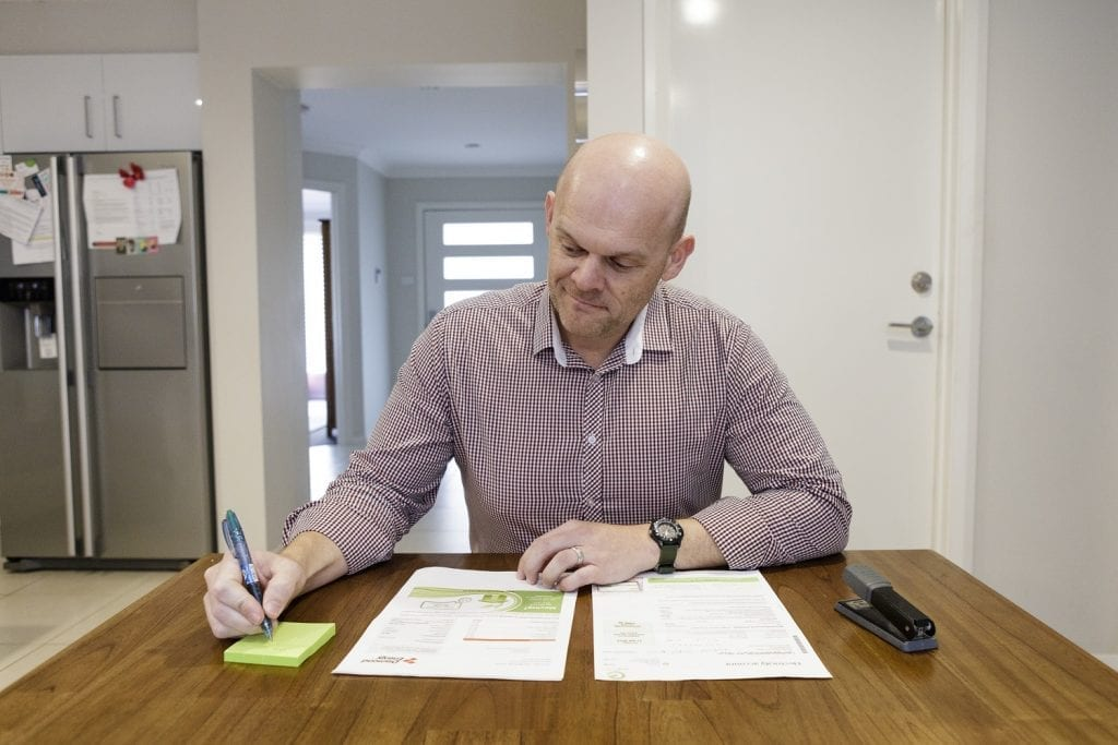 Nick Pfitzner reviewing the changes in his bills after installing a Tesla Powerwall by Natural Solar